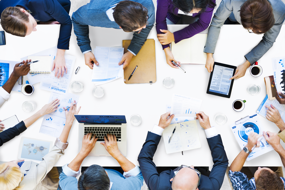 Image shows group of business people sitting around a crowded desk, each working on a project together collaboratively