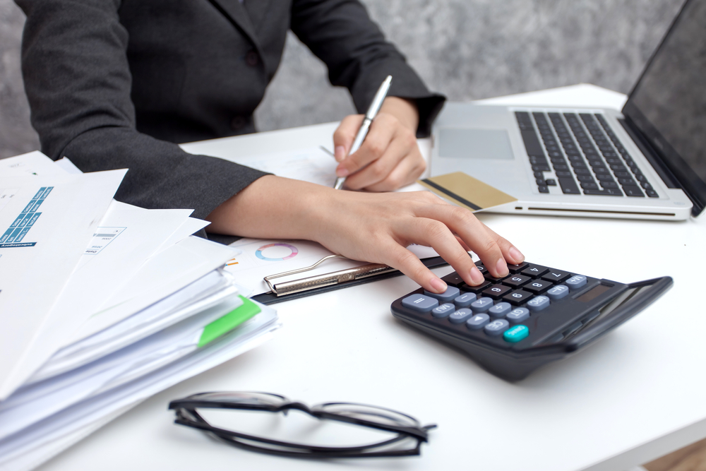 Image shows business woman at desk with laptop, calculator, and stack of business documents making calculations