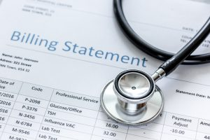 Image shows closeup of a medical billing statement with a stethoscope covering part of the bill
